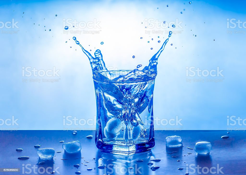 Ice splashing in a cool glass of water stock photo