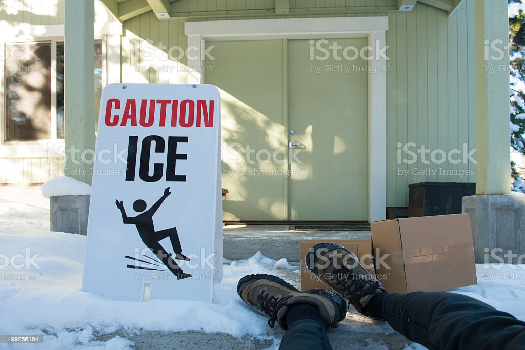 Ice warning sign with feet of fallen delivery person stock photo