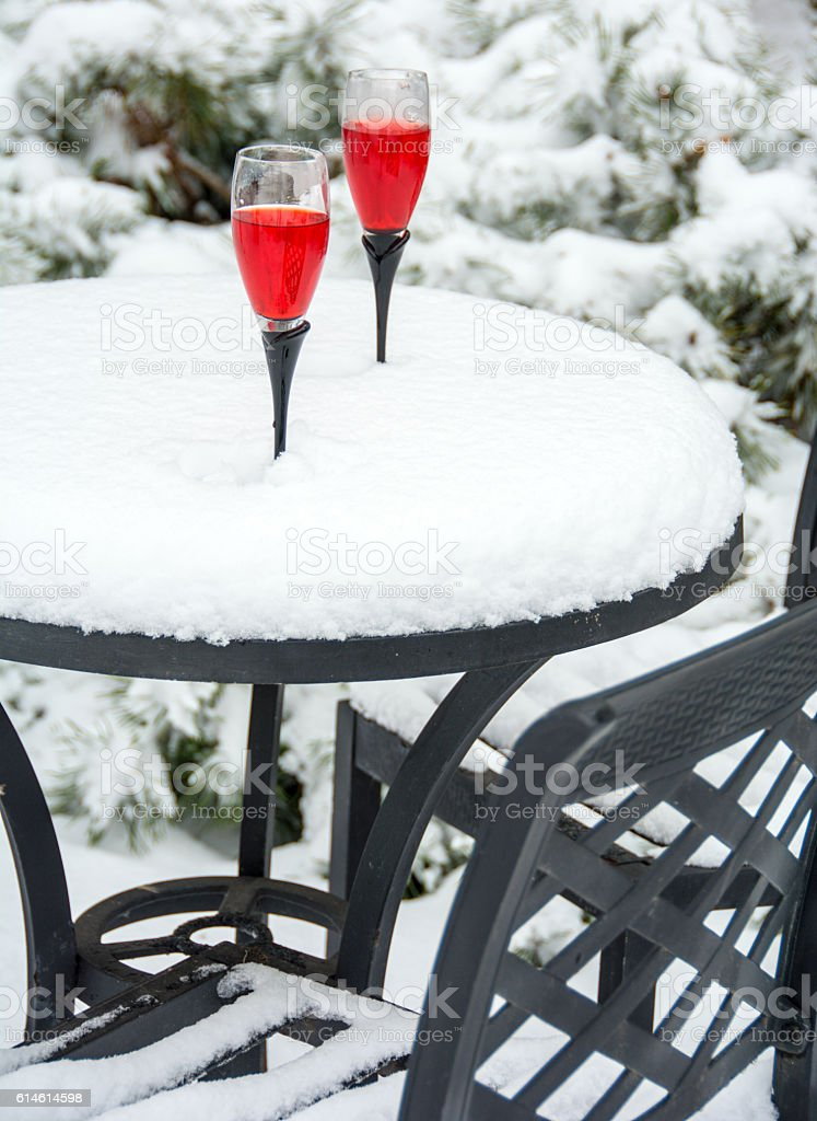 Ice wine glasses on a snow covered table-  copy space stock photo