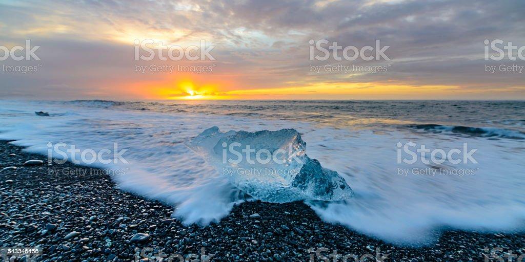 Iceberg block shape on the Jokulsarlong lava beach during sunrise stock photo