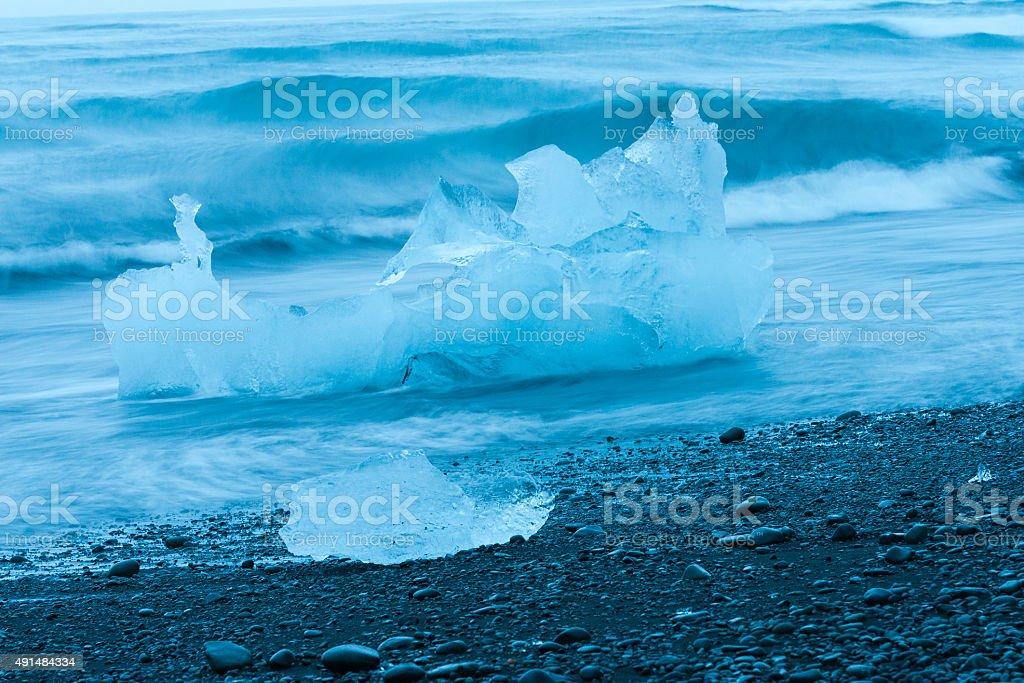 Iceberg chunks stranded on volcanic beach stock photo