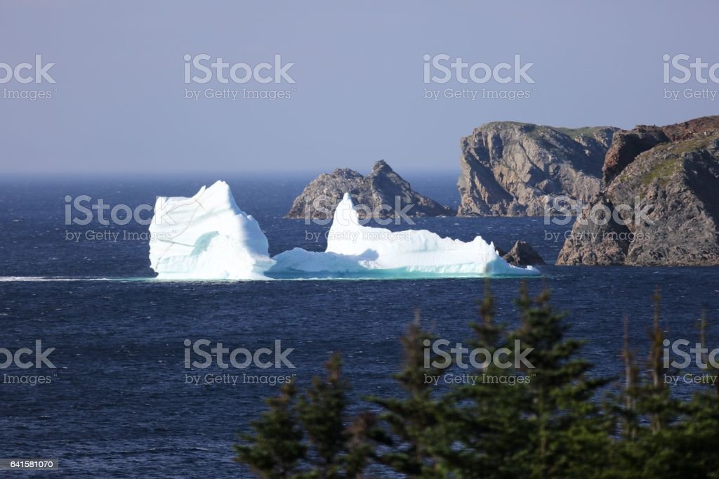 Iceberg in Newfoundland, next to rocky cliffs stock photo