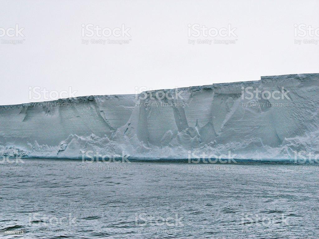 Iceberg wall against white sky stock photo