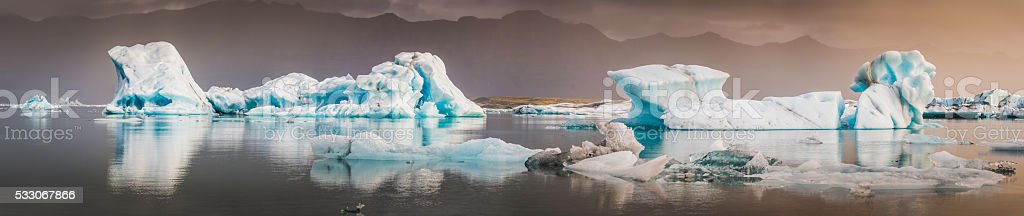 Icebergs creaking in Arctic ocean lagoon beneath sunset storm Iceland stock photo