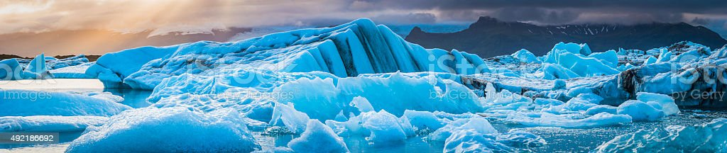 Icebergs floating in tranquil blue waters at sunset panorama Iceland stock photo