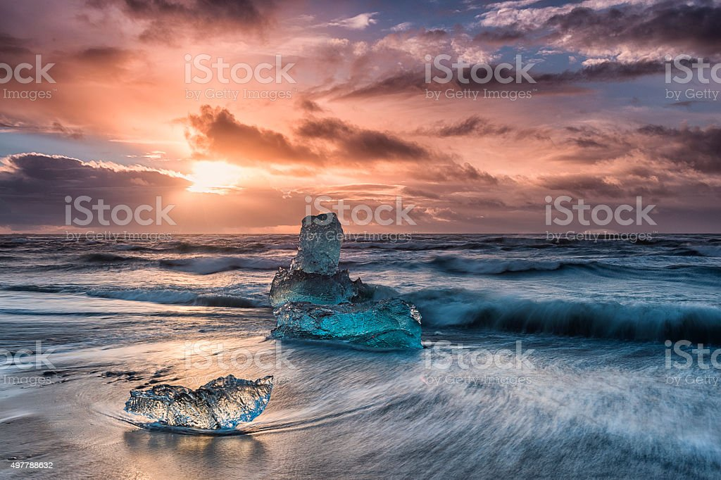Icebergs Floating on Icy Beach at Sunrise, South Iceland stock photo