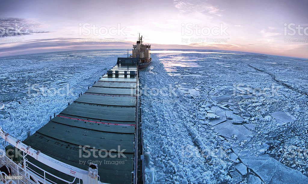 Icebreaker towing cargo ship through thick ice-field stock photo