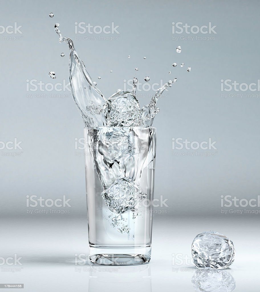 Ice-cube splashing into a glass filled with water. stock photo