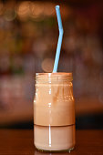 Iced coffee in glass jar on brown table