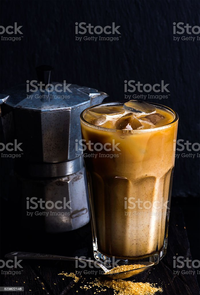 Iced coffee with milk in a tall glass, moka pot stock photo
