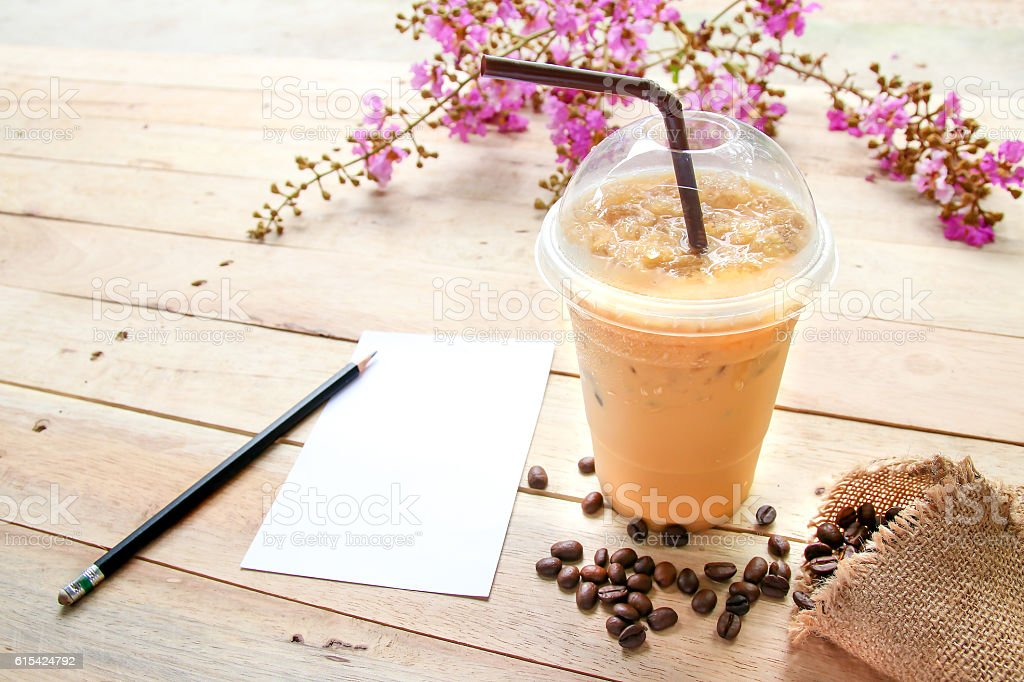 Iced coffee with pencil and paper on Wooden background. stock photo