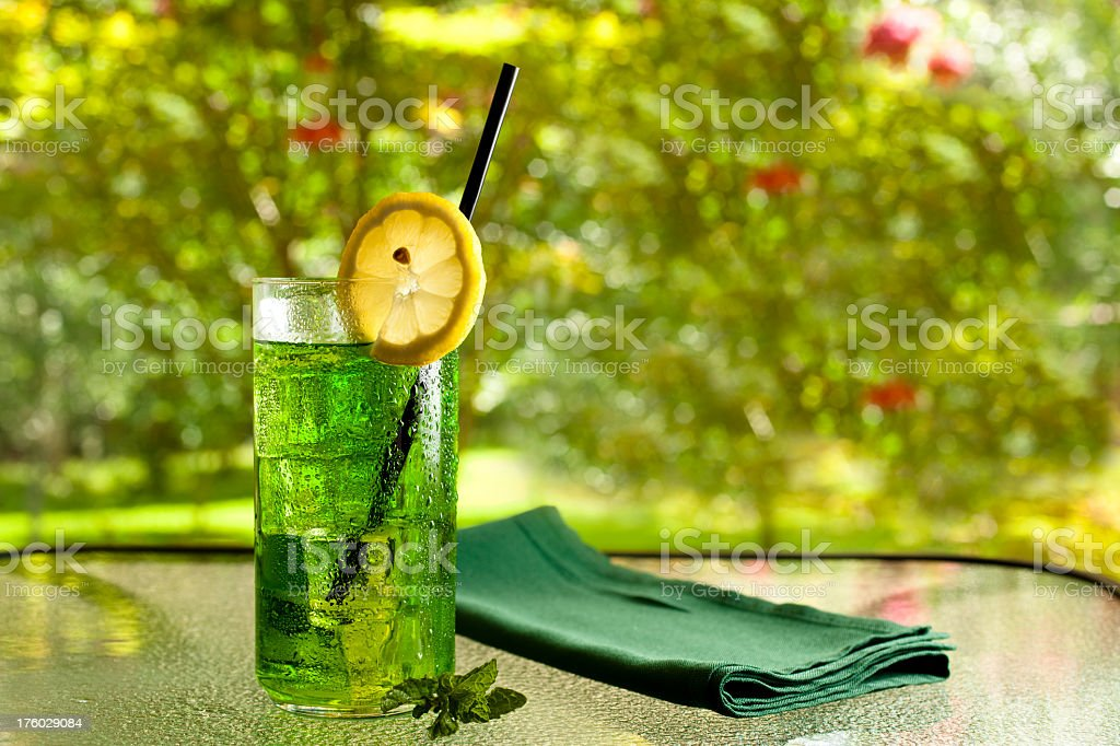 Iced cold green drink with lemon, mint  straw table napkin royalty-free stock photo