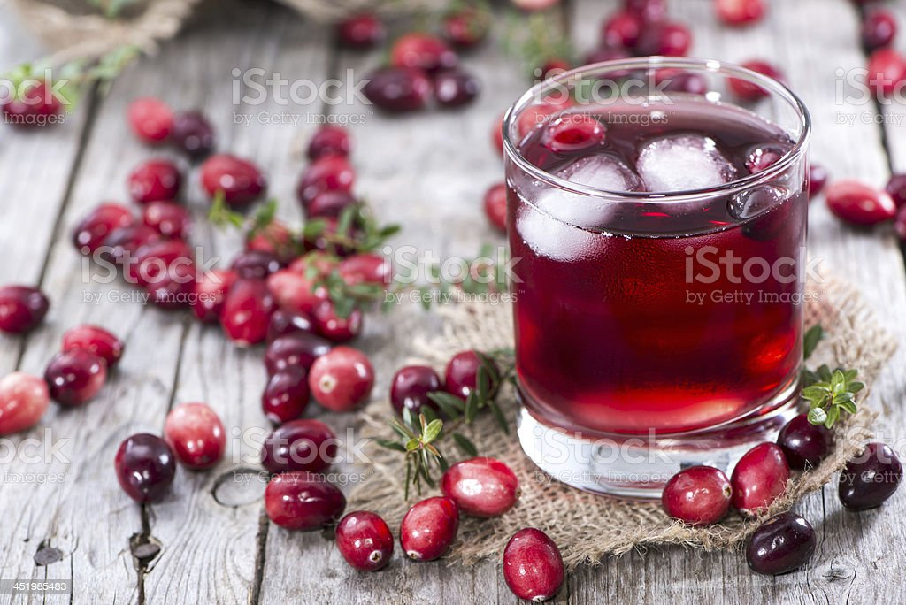 Iced glass of cranberry juice surrounded by cranberries stock photo