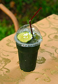 Iced lamon green tea with a straw on the table