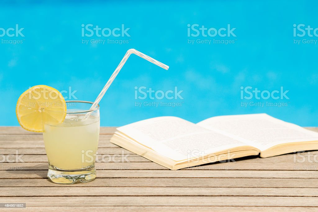 Iced lemonade and book on the table stock photo