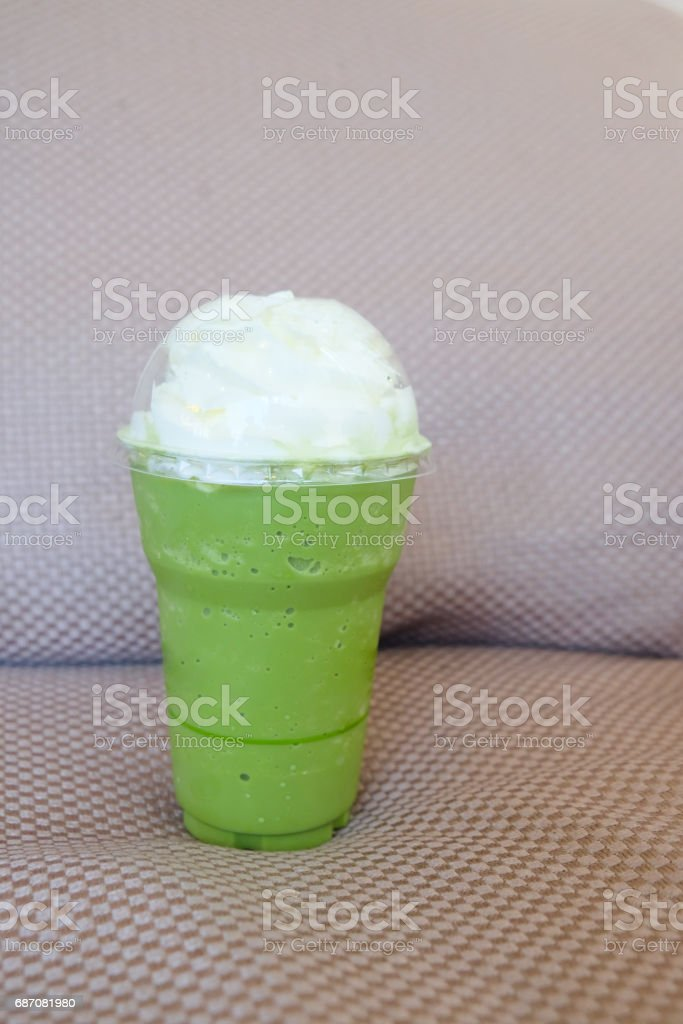 Iced matcha latte with coconut whipped cream stock photo