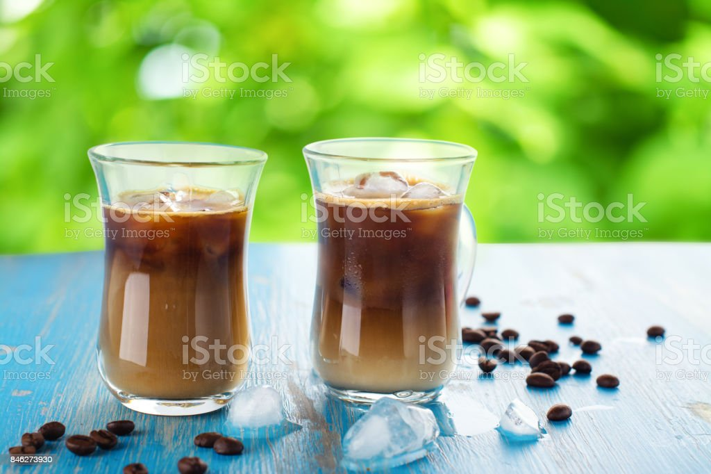 Iced coffee in a glass with cream over summer background