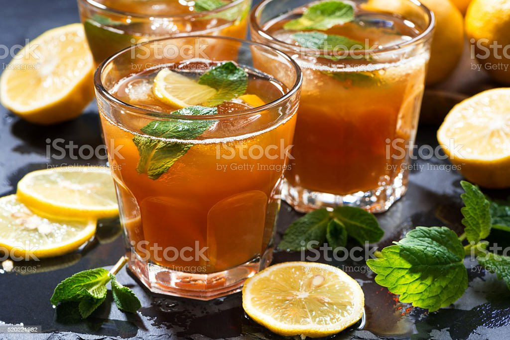iced tea with mint and lemon on dark background stock photo