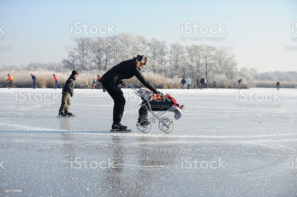 Ice-skating woman with baby stroller on a frozen lake royalty-free stock photo