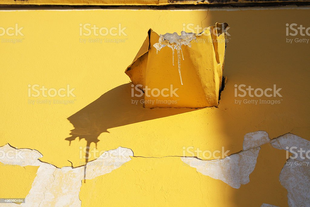 Icicle on yellow wall. stock photo