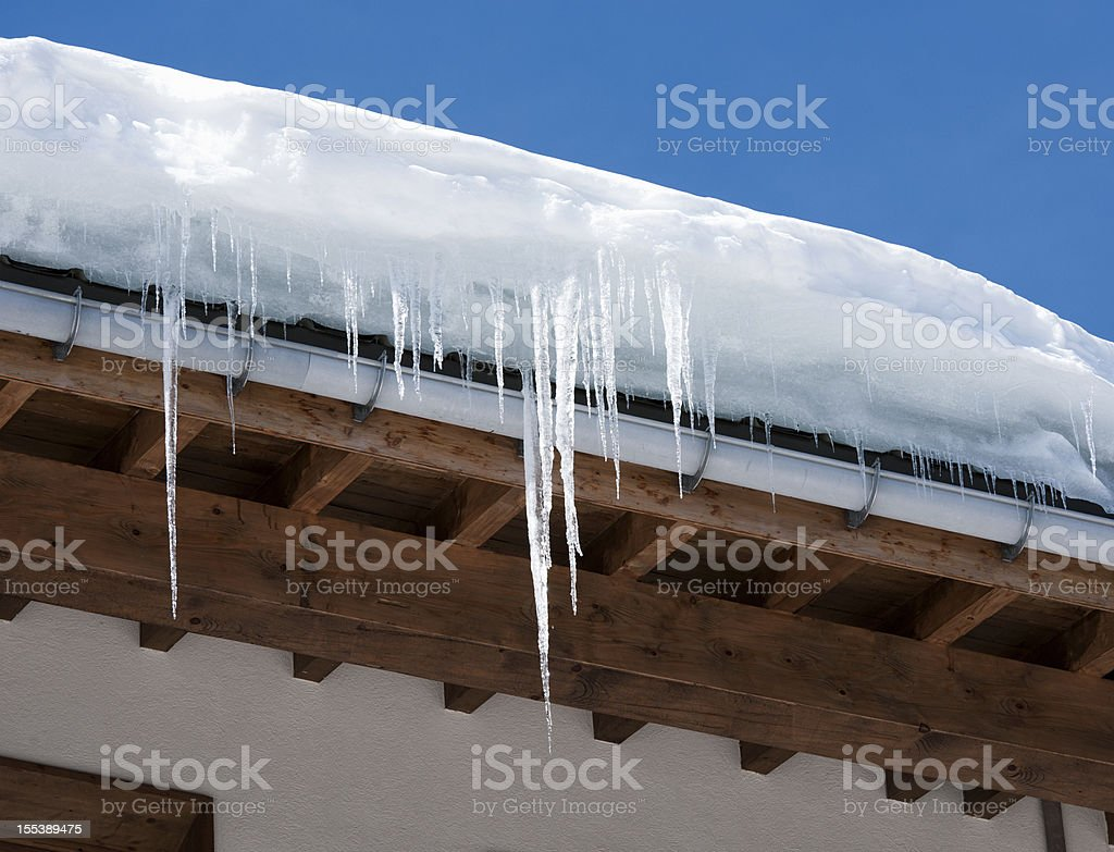 Icicles and Snow Overhanging a Roof royalty-free stock photo