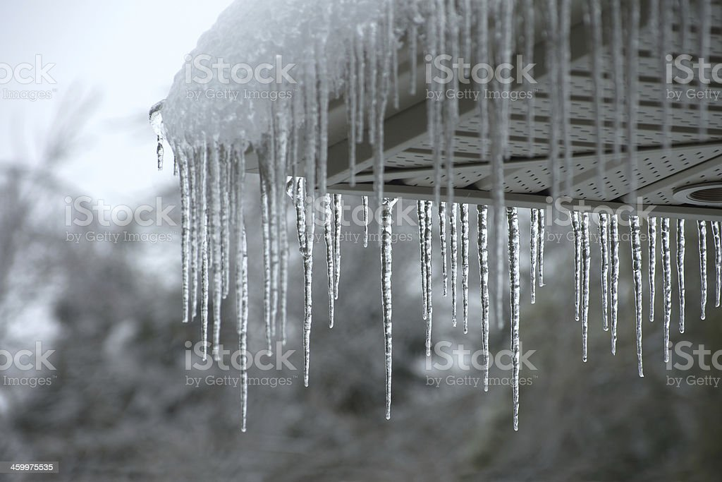 Icicles falling from a roof during winter stock photo
