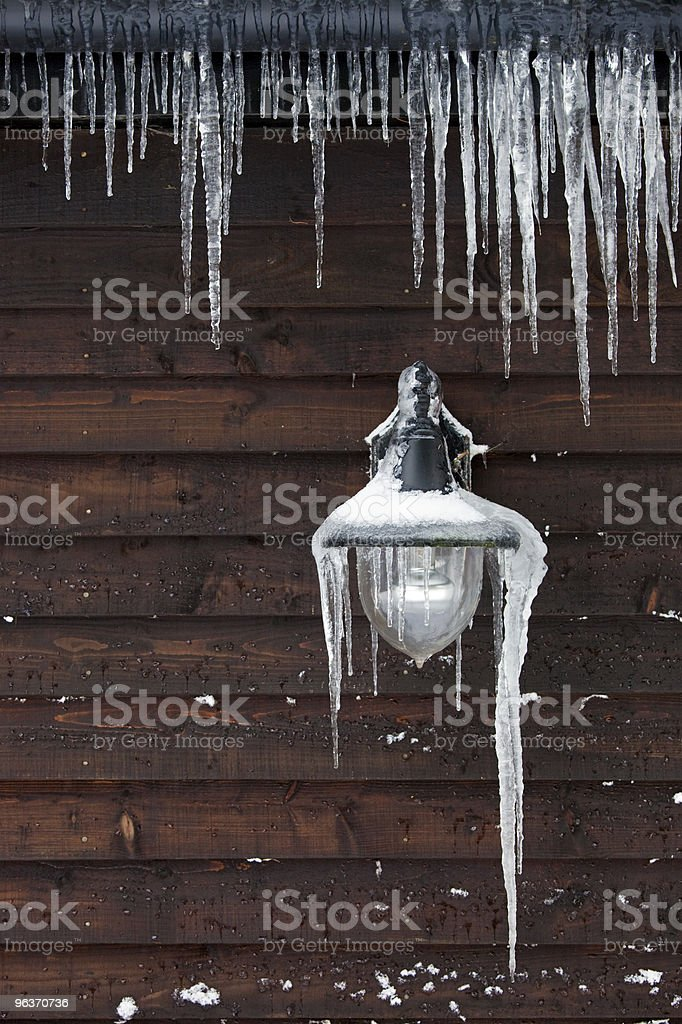 Icicles hanging from a lamp and drainpipe stock photo