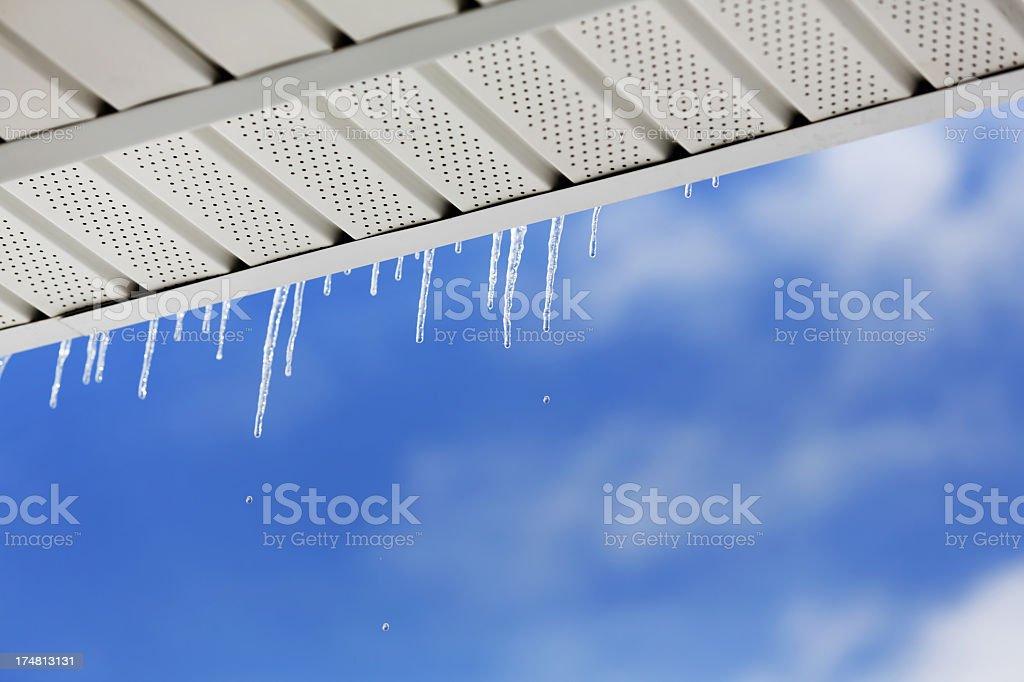Icicles Melting Under Eavestrough stock photo