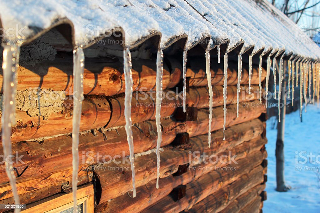 Icicles on slate roof of a log cabin stock photo