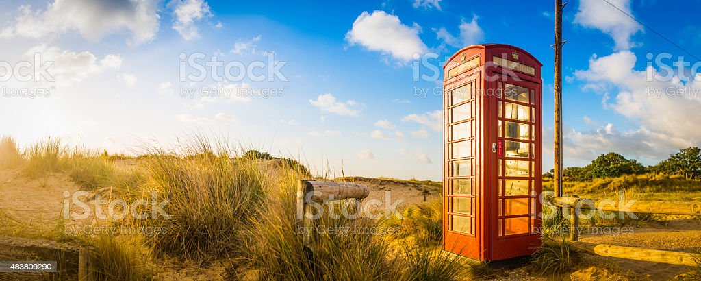 Iconic british red telephone box in idyllic summer beach dunes stock photo