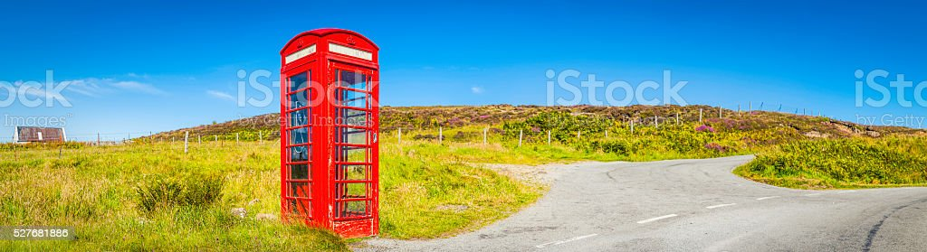 Iconic British red telephone box summer country road panorama UK stock photo