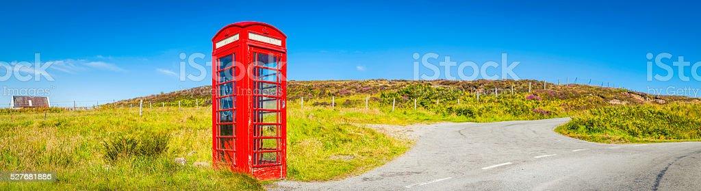 Iconic British red telephone box summer country road panorama UK stock photo