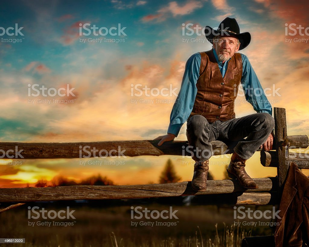 Iconic Cowboy Sitting On A Rail Fence In The Sunset stock photo