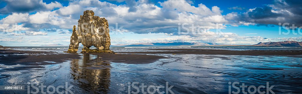 Iconic Hvitserkur sea stack reflecting in black beach panorama Iceland stock photo