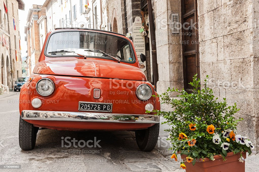 Iconic Italian orange Fiat car parked in traditional narrow stre stock photo