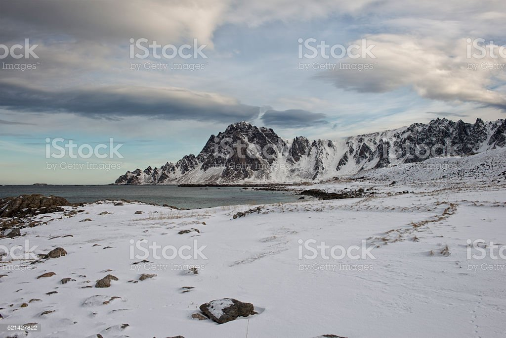 Icy Beach and Rocky Mountain. stock photo