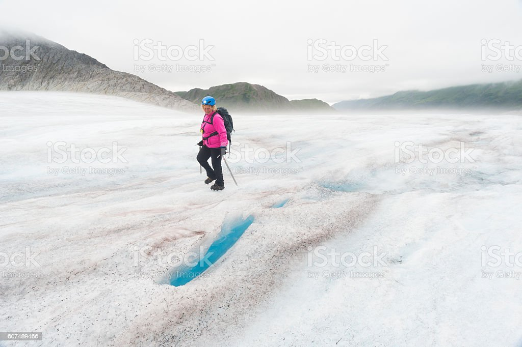 Icy glacier landscape with female trekker stock photo