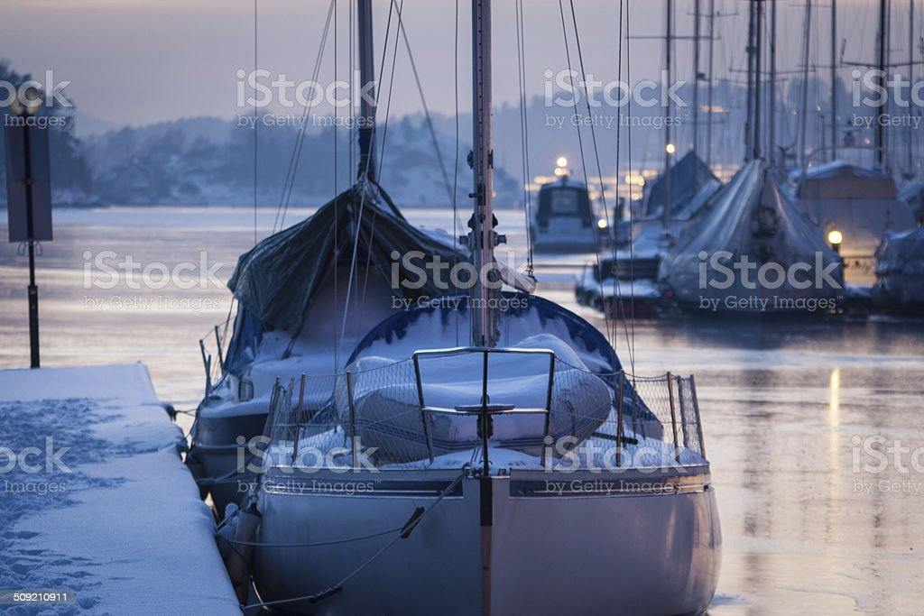 Icy pier and sailboats at sunset royalty-free stock photo