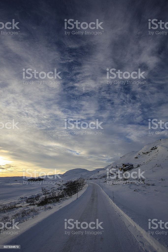 Icy road in the mountains at sunset royalty-free stock photo