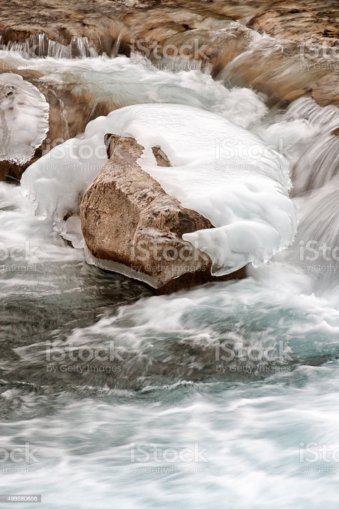 Icy Rock in River stock photo
