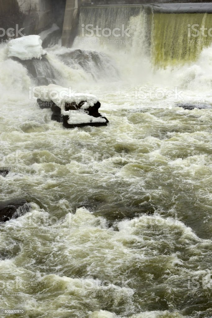 Icy Rock in Turbulent Waters at Sherbrooke Quebec Hydro (downtown Sherbrooke) Quebec, Canada stock photo