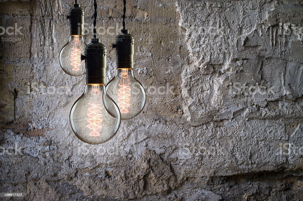 Idea concept - Vintage incandescent bulbs on wall background stock photo