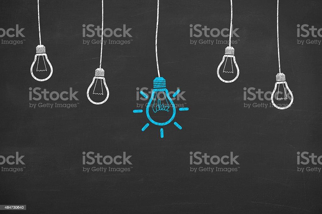 Idea Light Bulb Concept Drawing Working on Blackboard stock photo