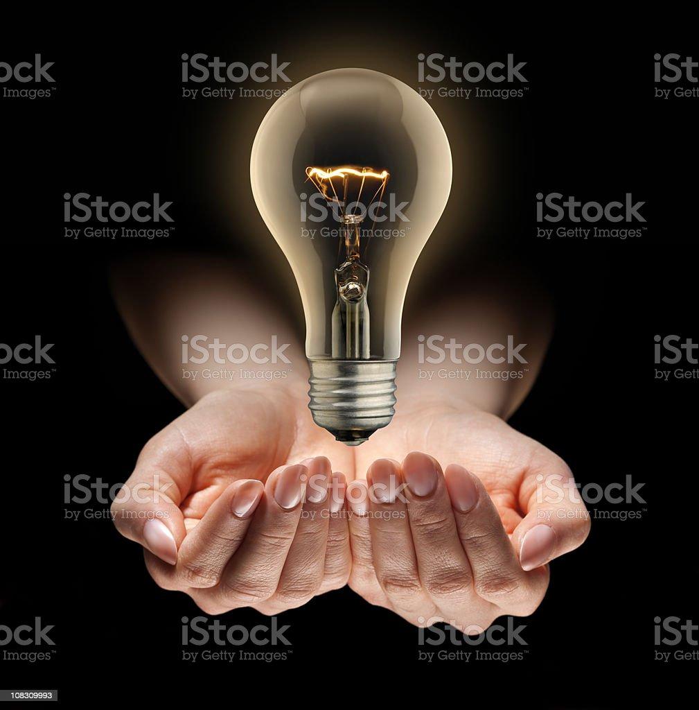 Idea Light Bulb Levitating Over Nurturing Hands stock photo
