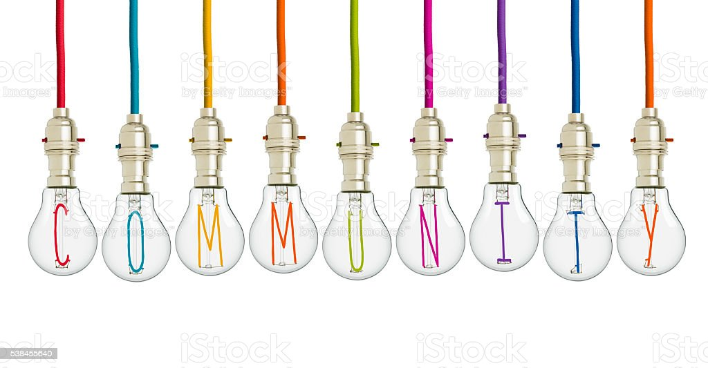 COMMUNITY ideas brought together in different coloured light bulbs stock photo