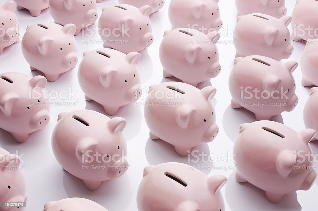 Identical pink ceramic piggy banks standing in rows royalty-free stock photo