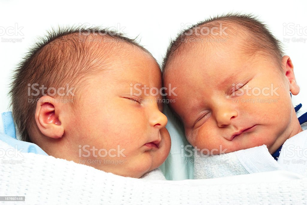 Identical twin baby boys lying close together stock photo