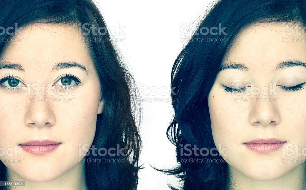 Identical twins posing, one with eyes open, the other closed stock photo