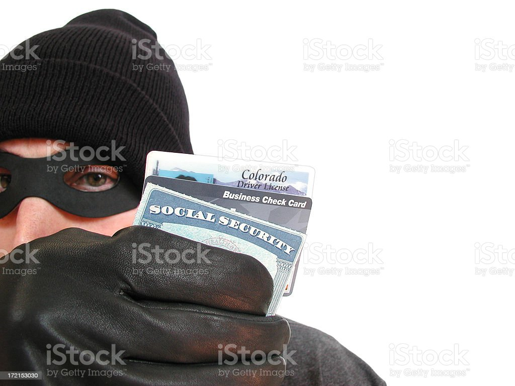 Identity Theft: Masked Thief Holds License and Social Security Card royalty-free stock photo