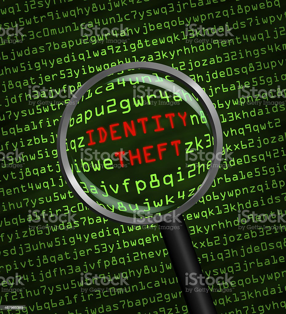 Identity Theft revealed in computer code through magnifying glass stock photo